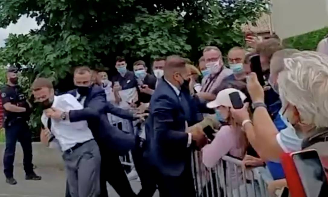 O presidente da França, Emmanuel Macron, é protegido por seguranças após levar um tapa no rosto de um homem no Sul do país Foto: BFMTV/ReutersTV / Via REUTERS