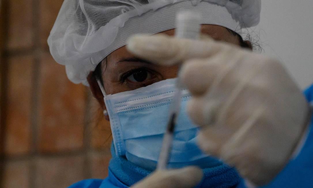 Profissional de saúde prepara uma dose da vacina da Pfizer/BioNTech contra a Covid-19 em Paso de Carrasco, departamento de Canelones, Uruguai, em maio de 2021 Foto: EITAN ABRAMOVICH / AFP