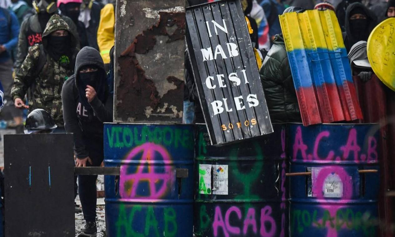 Manifestantes com escudos enfrentam a tropa de choque durante um protesto contra o governo do presidente colombiano Iván Duque, em Bogotá Foto: JUAN BARRETO / AFP