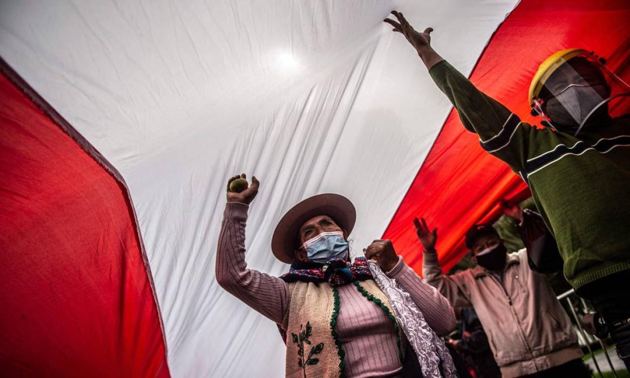 Apoiadores do candidato presidencial peruano de esquerda pelo partido Peru Libre, Pedro Castillo, protestam em frente ao prédio do Júri Eleitoral Nacional em Lima. Com mais de 99% dos votos apurados, a diferença entre os candidatos é de 0,5% Foto: ERNESTO BENAVIDES / AFP