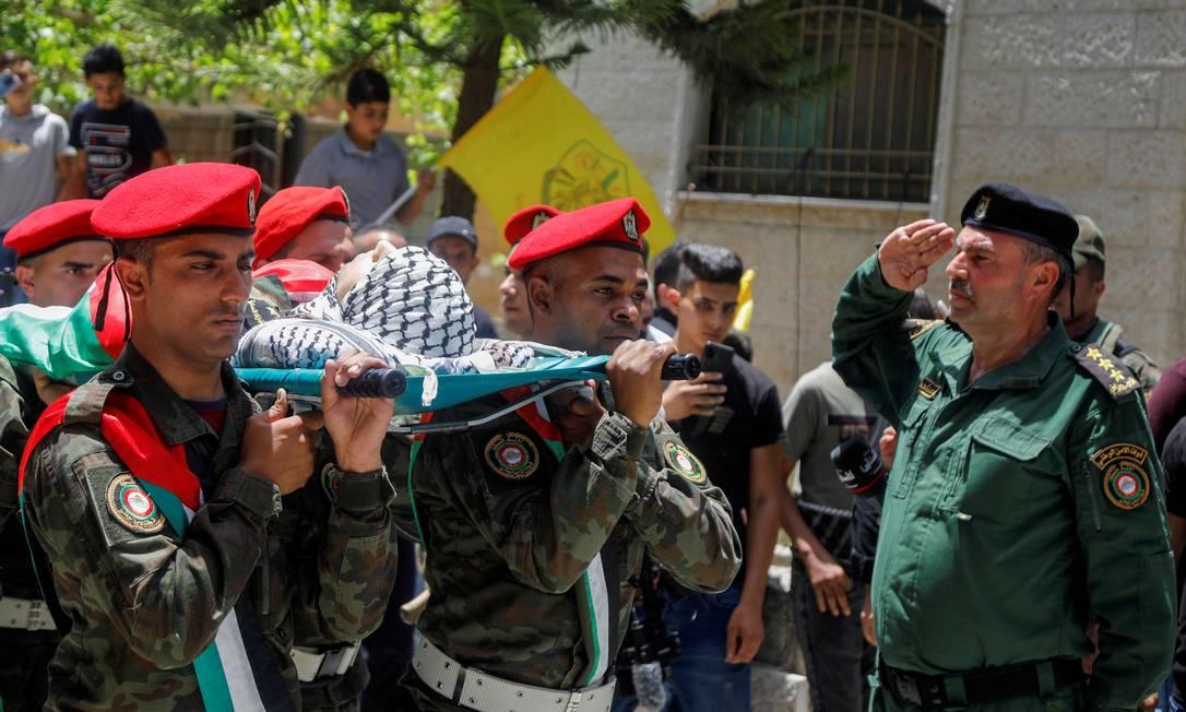 Militares palestinos carregam o corpo de Adham Alioh, morto durante conflito com forças israelenses na Cisjordânia ocupada Foto: RANEEN SAWAFTA / REUTERS
