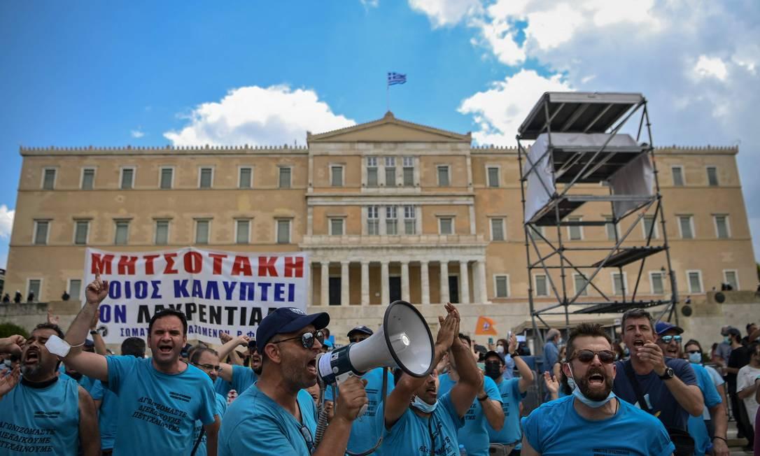 Manifestante usa megafone para emitir palavrasas de ordem durante protesto contra reforma trabalhista em Antenas, na Grécia Foto: ARIS MESSINIS / AFP