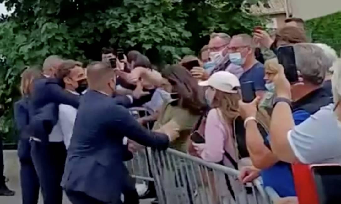 Emmanuel Macronn é protegido por seguranças após receber tapa de Damien Tarel, que aparece com camiseta câqui na imagem Foto: BFMTV/ReutersTV / Via REUTERS
