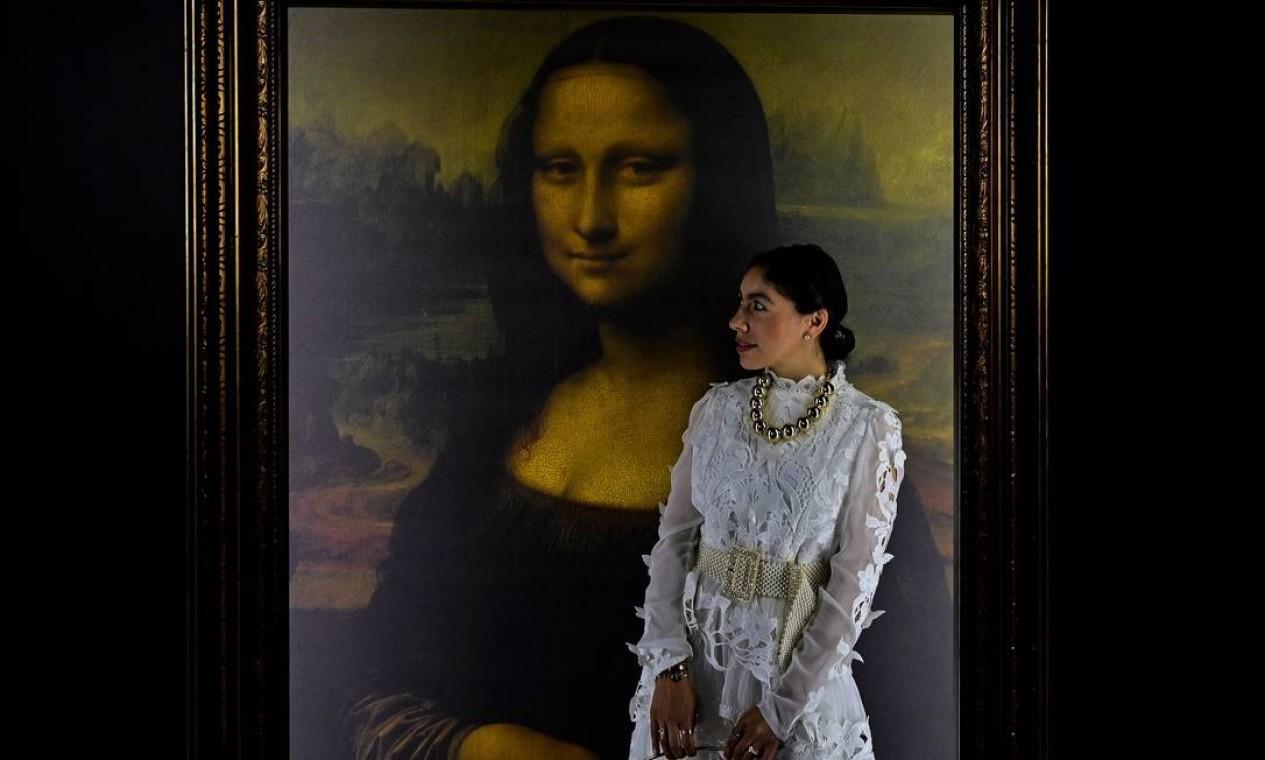 Mulher posa para fotos ao lado de uma reprodução da Mona Lisa. O retrato de Lisa Gherardini, esposa de Francesco del Giocondo, conhecida também como La Gioconda está exposto na DaVinci Experience na Cidade do México Foto: PEDRO PARDO / AFP