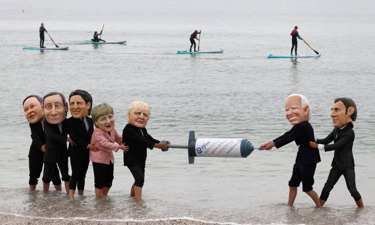 Ativistas fantasiados dos líderes do G7 performam brigam por uma seringa de vacina COVID-19 na praia de Swanpool em Falmouth, Cornwall, à margem da cúpula do G7 Foto: ADRIAN DENNIS / AFP