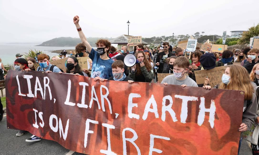 Ativistas ambientais da Cornwall Youth Climate Alliance participam de um protesto de Fridays For Future na praia de Gyllyngvase, em Falmouth, sudoeste da Inglaterra, no primeiro dia da cúpula de três dias do G7 Foto: ADRIAN DENNIS / AFP