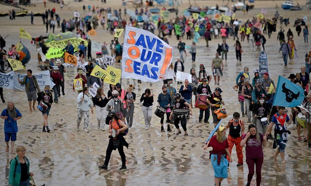 Ativistas marcham em protesto em Cornualha, no primeiro dia da cúpula do G7 Foto: BEN STANSALL / AFP