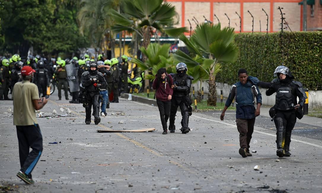 Policiais colombianos prendem manifestantes durante protesto contra o governo em Cali, 9 de junho Foto: LUIS ROBAYO / AFP