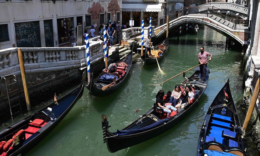 Turistas passeiam numa gôndola em Veneza, no começo de junho Foto: MIGUEL MEDINA / AFP