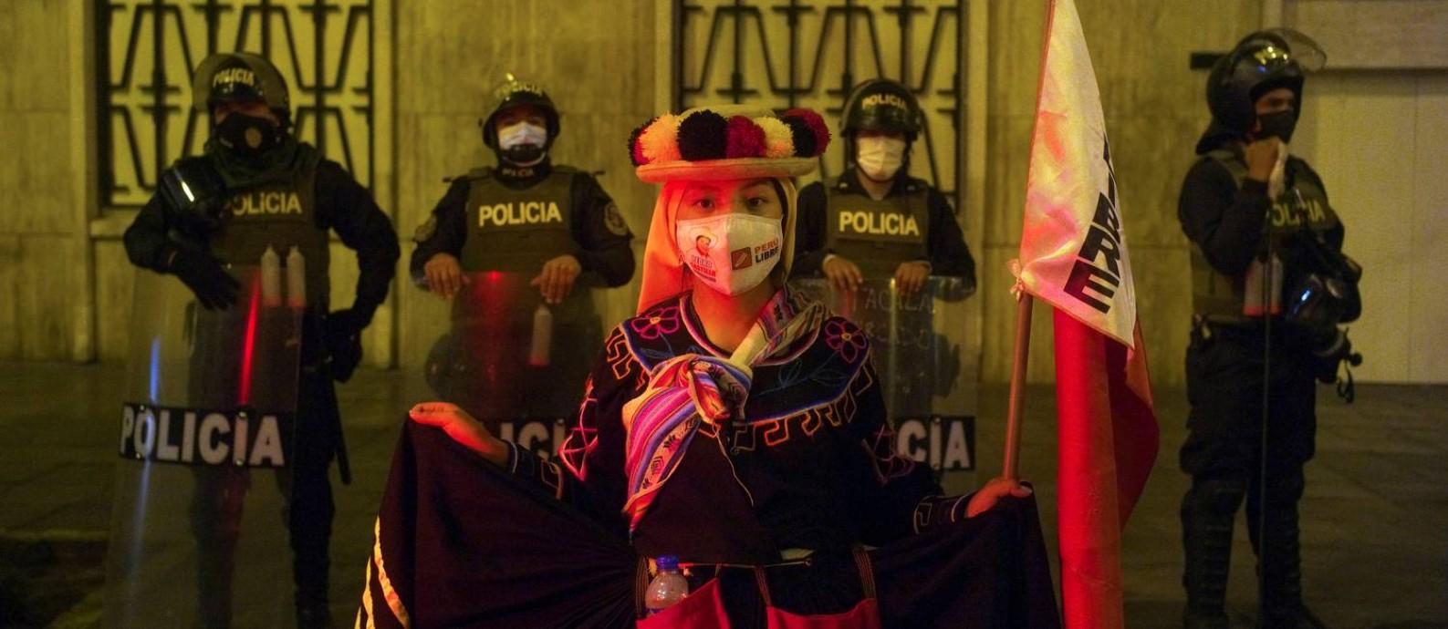 Apoiadora de Pedro Castillo se manifesta em frente a policiais que guardam a sede do Escritório Nacional de Processos Eleitorais Foto: ALESSANDRO CINQUE / REUTERS/9-6-2021