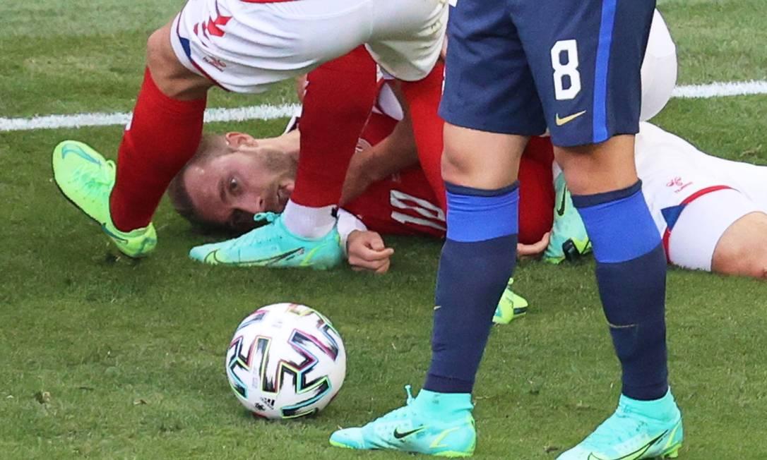 Eriksen é atendido por jogadores logo depois de cair desacordado em partida da Eurocopa Foto: WOLFGANG RATTAY / Pool via REUTERS