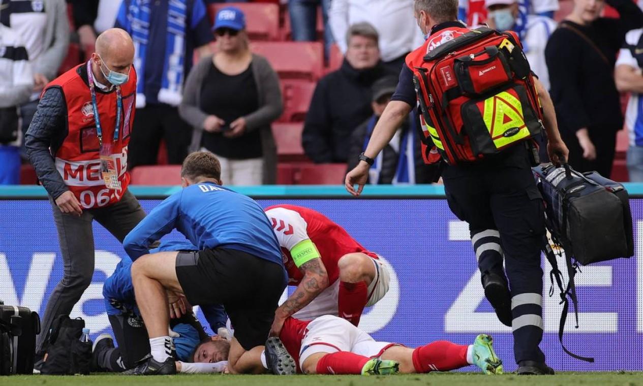 Paramédicos se aproximam do meio-campista Christian Eriksen após ele ter desmaiado em campo Foto: FRIEDEMANN VOGEL / AFP