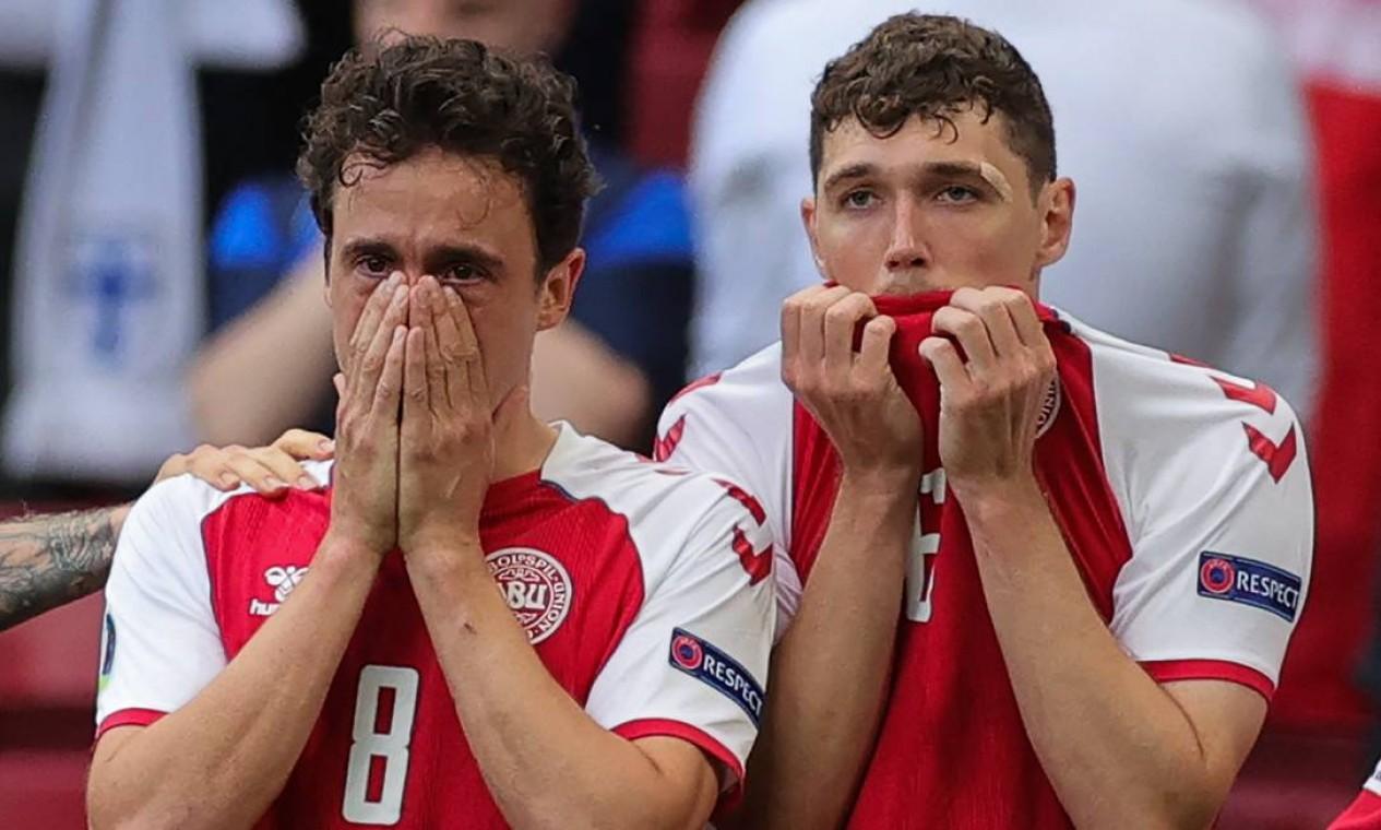 O meio-campista Thomas Delaney e o zagueiro Andreas Christensen choram preocupados com o companheiro Eriksen Foto: FRIEDEMANN VOGEL / AFP