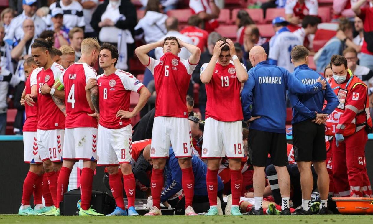 Jogadores da Dinamarca aguardam ansiosos o atendimento médico ao companheiro Christian Eriksen, após ele ter desmaiado em campo durante a partida do Grupo B da Eurocopa, entre Dinamarca e Finlândia, no Estádio Parken, em Copenhague Foto: FRIEDEMANN VOGEL / AFP