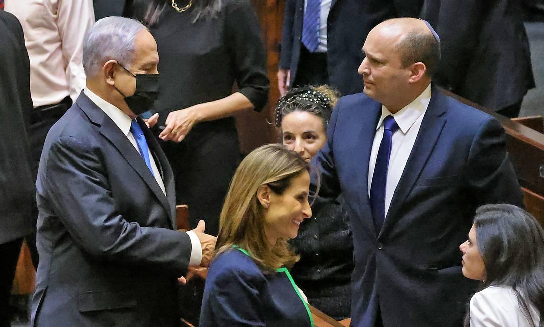 """Netanyahu (à esquerda) cumprimenta seu sucessor, Naftali Bennett, cujo """"governo ruim"""" prometeu derrubar em discurso após ser afastado do cargo Foto: EMMANUEL DUNAND / AFP"""