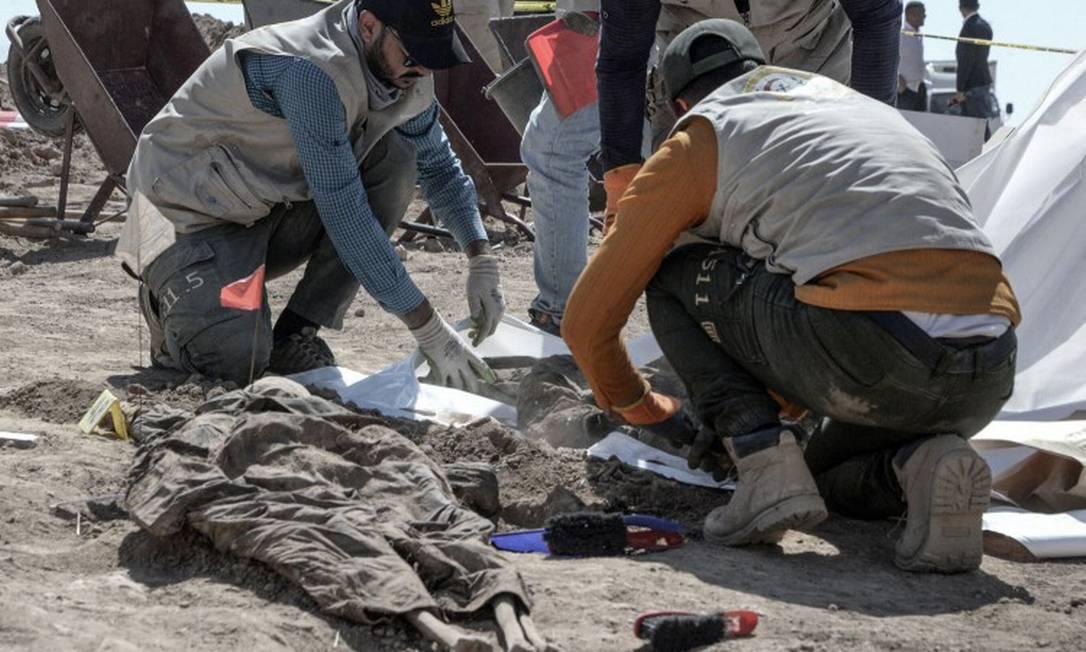Funcionários trabalham na remoção e identificação de vítimas do Estado Islâmico Foto: ZAID AL-OBEIDI / AFP