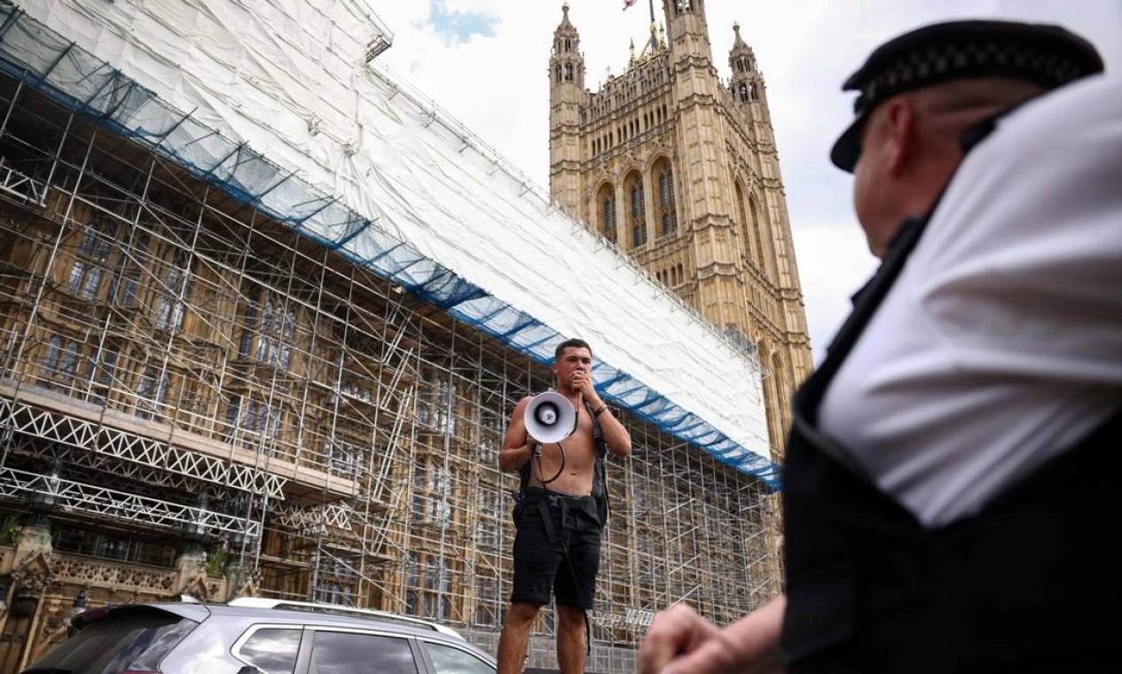 Um manifestante usa um megafone durante um protesto perto do Parlamento. Diante do aumento de casos de Covid-19 no Reino Unido, o primeiro-ministro, Boris Johnson, anunciou, nesta segunda-feira, o adiamento do fim das restrições anticovid Foto: HENRY NICHOLLS / REUTERS