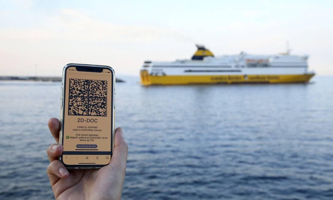 Uma mulher segura o celular com o código QR que mostra o resultado de teste negativo para Covid-19, necessário para embarcar numa barca na Córsega Foto: PASCAL POCHARD-CASABIANCA / AFP