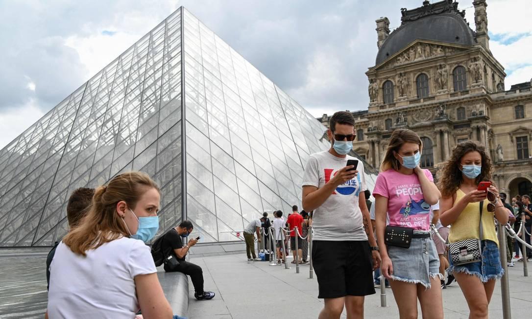 De máscaras, pessoas caminham em frente a Pirâmide do Museu do Louvre, projeto do renomado arquiteto Ieoh Ming Pei Foto: BERTRAND GUAY / AFP/16-8-2020