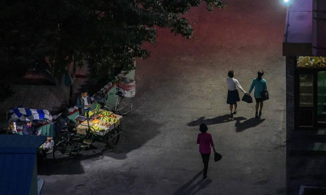 Pedestres caminham próximos a uma barraca de frutas em Pyongyang Foto: ED JONES / AFP