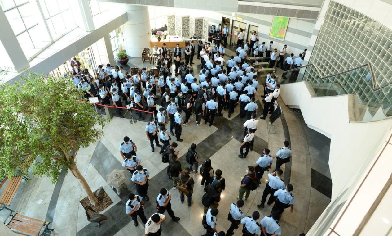 Policiais se reúnem na sede do Apple Daily, em Hong Kong, China Foto: APPLE DAILY / VIA REUTERS