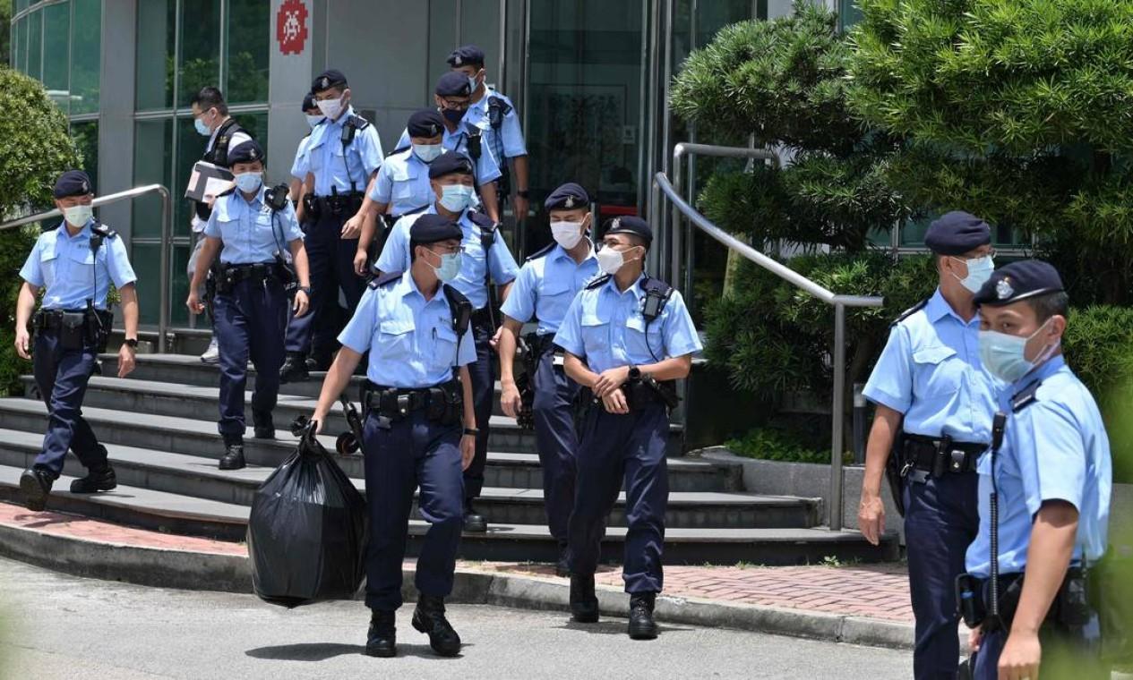Policiais deixam os escritórios do jornal Apple Daily em Hong Kong com apreensões, depois de dois executivos e três editores serem presos Foto: ANTHONY WALLACE / AFP