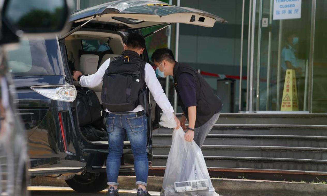 Policiais do departamento de segurança nacional colocam itens apreendidos em uma van da polícia em frente aos escritórios do Apple Daily e Next Media em Hong Kong Foto: LAM YIK / REUTERS