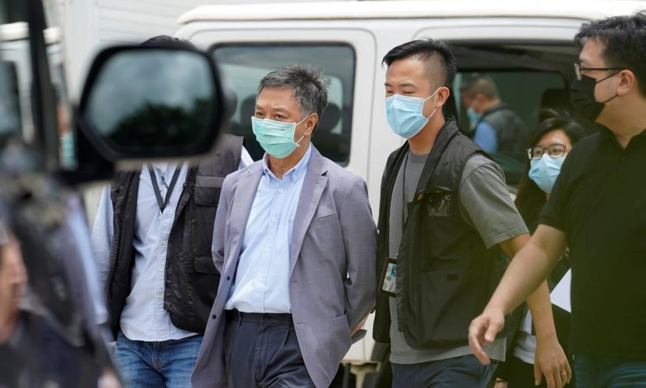 Policiais do departamento de segurança nacional escoltam o chefe de operações Chow Tat-kuen dos escritórios do Apple Daily e Next Media em Hong Kong, China Foto: LAM YIK / REUTERS