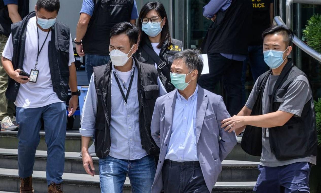 O chefe de operações do Apple Daily, Chow Tat Kuen é escoltado pela polícia até um veículo que esperava nos escritórios do jornal local Apple Daily em Hong Kong Foto: ANTHONY WALLACE / AFP