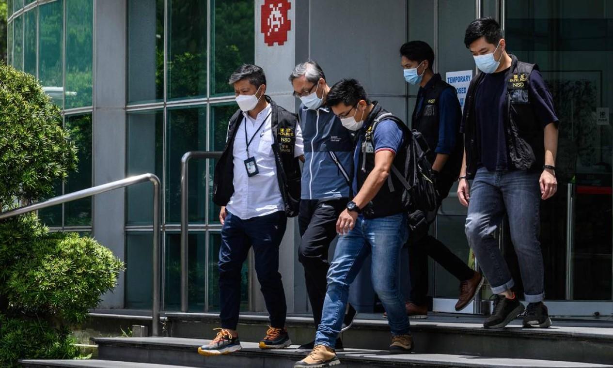 Cheung Kim Hung, CEO e diretor executivo da Next Digital Limited, é escoltado pela polícia dos escritórios do jornal local Apple Daily Foto: ANTHONY WALLACE / AFP