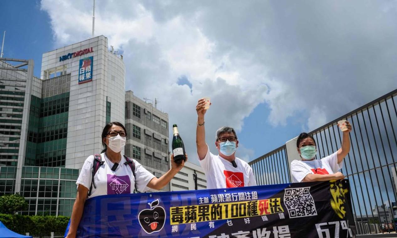 Ativistas pró-governo comemoram com champanhe fora dos escritórios do jornal local Apple Daily Foto: ANTHONY WALLACE / AFP