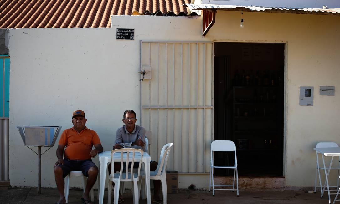 Moradores sentados à calçada observam policiais em buscas do assassino em série na cidade que pouco mais de 18 mil habitantes Foto: Pablo Jacob / Agência O Globo