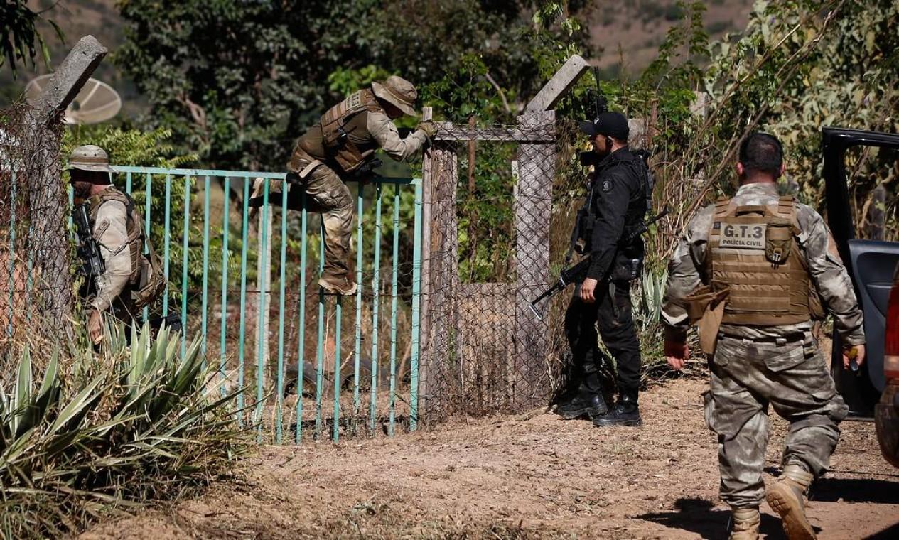 Policiais vasculham propriedade trancada em busca do criminoso Foto: Pablo Jacob / Agência O Globo