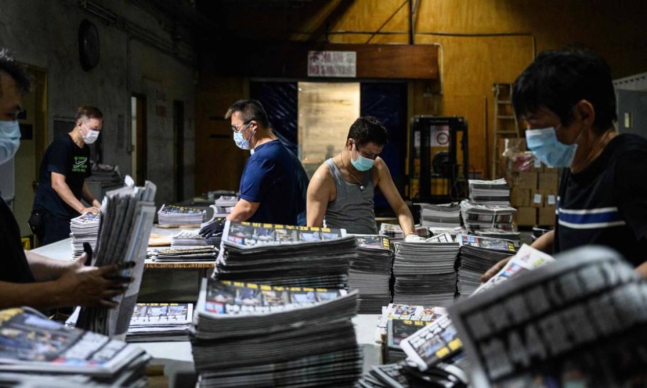 Funcionários compilam diferentes seções de jornais recém-impressos na gráfica dos escritórios do jornal Apple Daily em Hong Kong no início de 18 de junho de 2021, depois que a polícia prendeu o editor-chefe e quatro executivos do jornal pró-democracia na manhã anterior, fazendo uma batida sua redação pela segunda vez no golpe mais recente contra o tablóide franco. (Foto de Anthony WALLACE / AFP) / Acompanhando a história da AFP Hong Kong-China-political-media, FOCUS de Jerome TAYLOR Foto: ANTHONY WALLACE / AFP