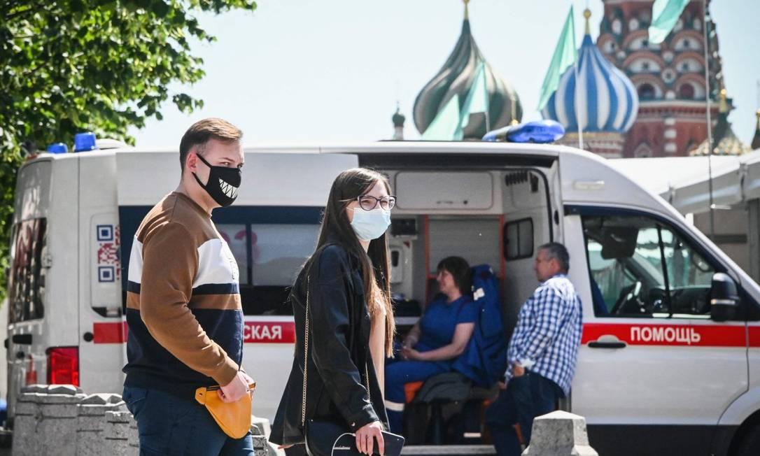 De máscara, pessoas caminham em frente à Catedral de São Basílico, em Moscou Foto: ALEXANDER NEMENOV / AFP/18-6-21