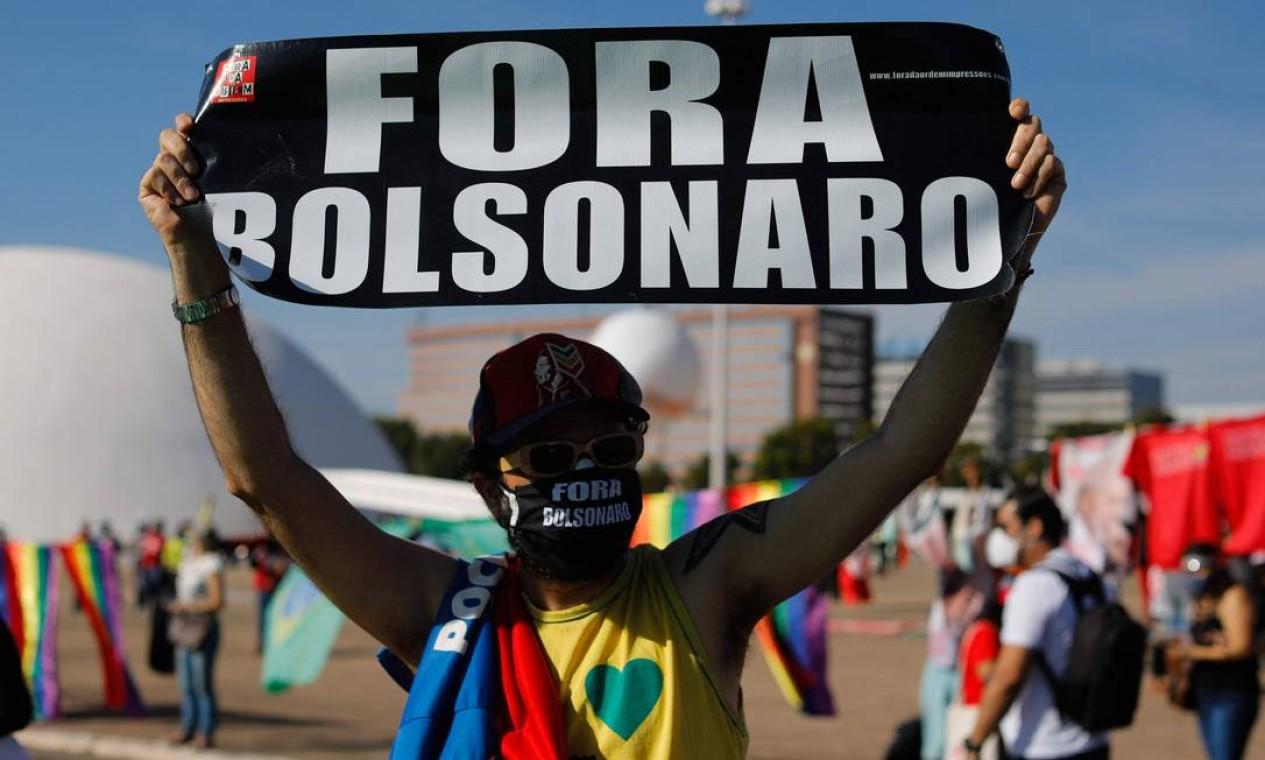 Em Brasília, ativista segura cartaz durante protesto contra a polírica de combate à pandemia. Atos contra o governo Bolsonaro acontecem simultaneamente neste sábado em diversas cidades do Brasil Foto: Sergio Lima / AFP