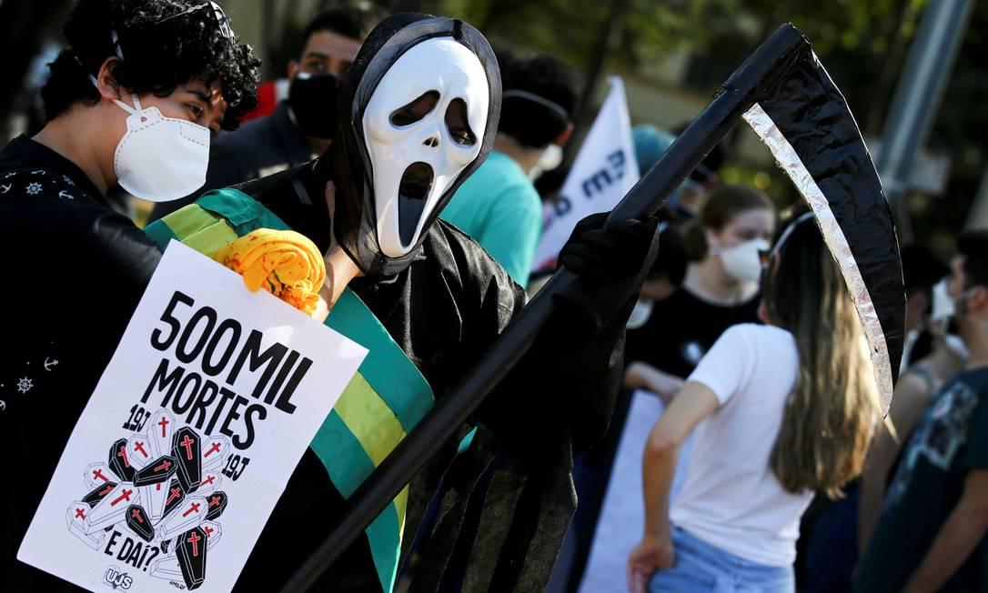 """Em Goiânia (GO), manifestante vestido como personagem do filme """"Pânico"""" e com faixa presidencial segura um cartaz referindo-se às 500 mil mortes provocadas pela pandemia de Covid-19 e a má gestão do governo Bolsonaro no combate ao coronavírus no país Foto: Diego Vara / Reuters"""