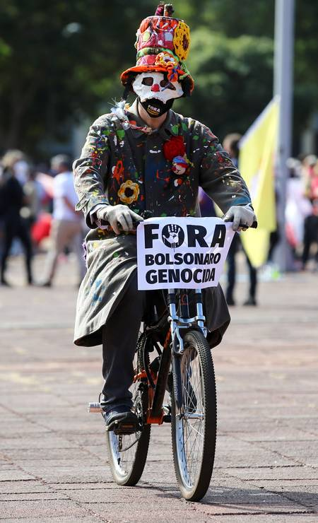 """Manifestante de bicicleta com uma placa """"Fora Bolsonaro Genocida"""" durante ato em Goiânia Foto: Diego Vara / Reuters"""