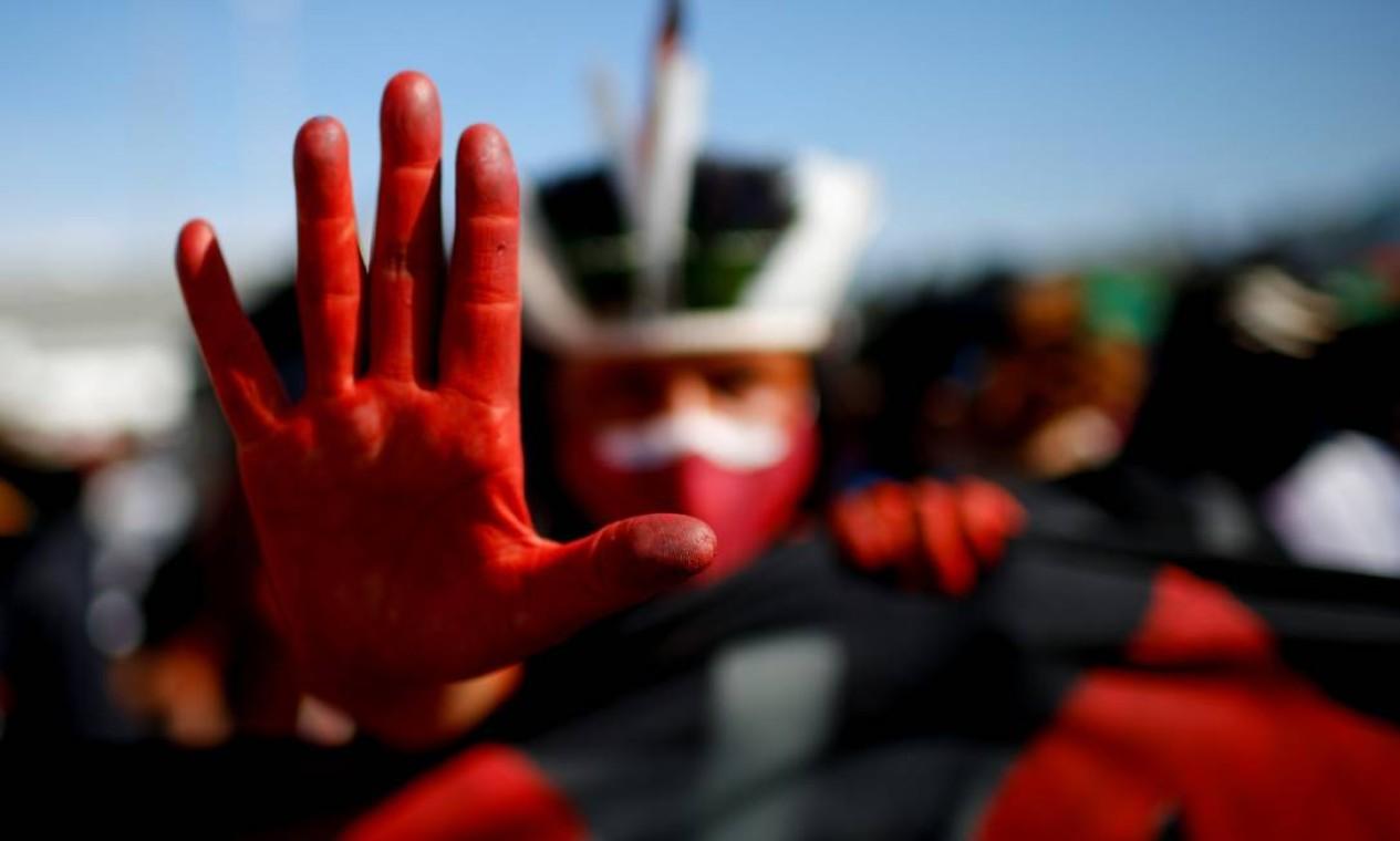 Indígena brasileiro faz sinal de basta com as mãos tingidas de vermelho durante protesto em Brasília pelas 500 mil mortes por Covid no país Foto: ADRIANO MACHADO / REUTERS