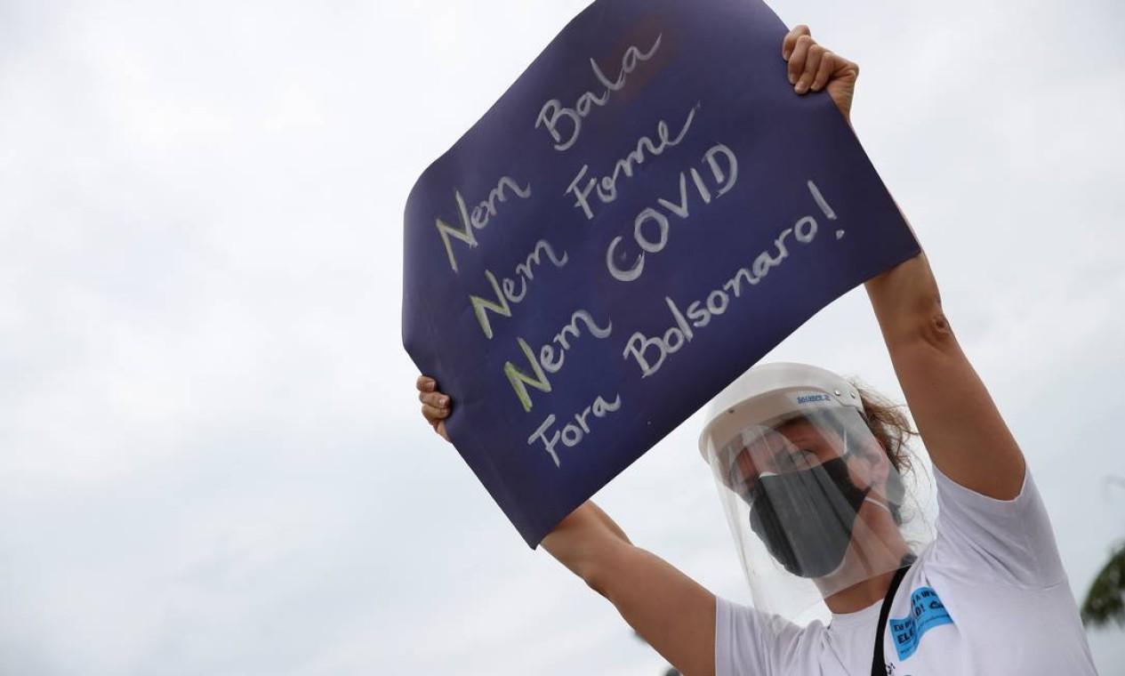 """Mulher exibe cartaz com as frases """"Nem bala, Nem fome, Nem Covid, Fora, Bolsonaro!"""" durante um manifestação na área central do Rio de Janeiro Foto: RICARDO MORAES / REUTERS"""