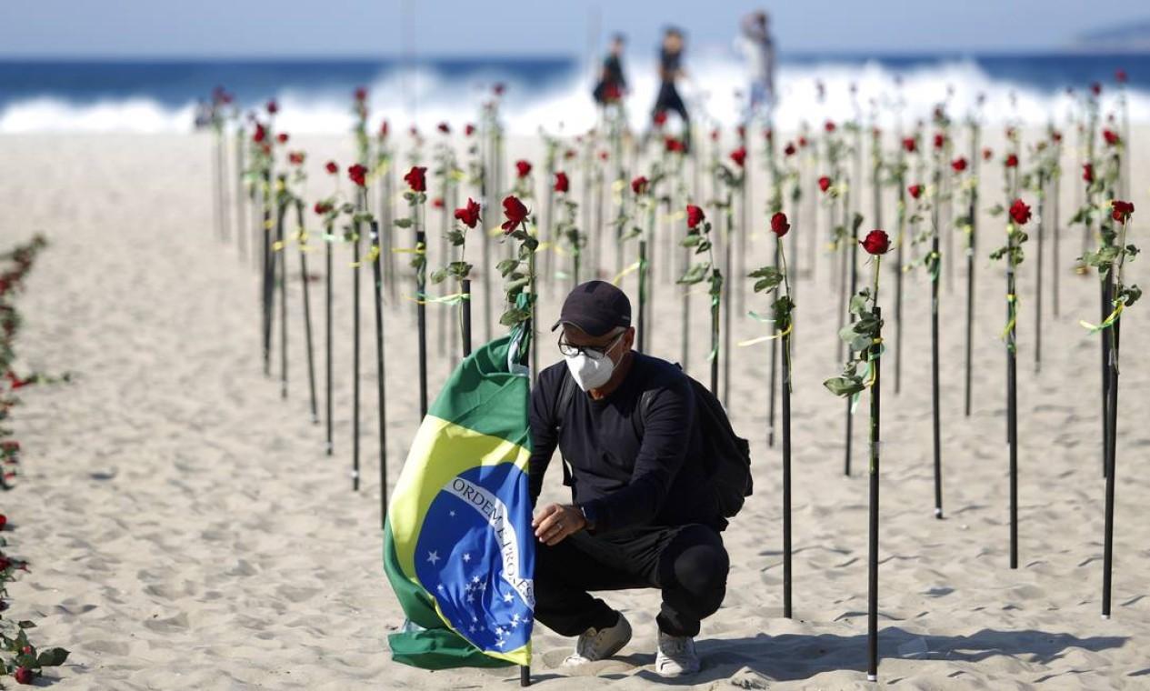 O pastor Antônio Carlos Costa, presidente da ONG, arruma um bandeira do Brasil junto a uma rosa na praia de Copacabana Foto: Fabio Rossi / Agência O Globo