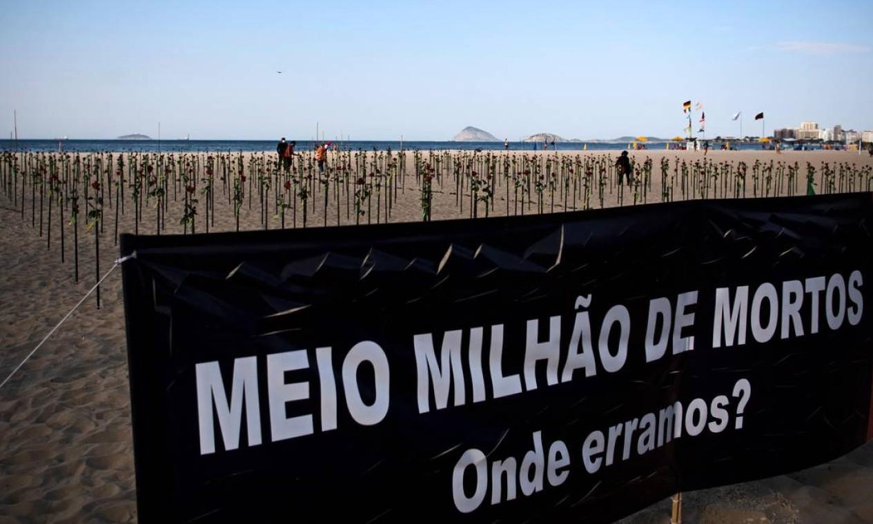 """Cartaz diz """"Meio milhão de mortos. Onde erramos?"""" ao lado das rosas colocadas pela ONG Rio de Paz na praia de Copacabana Foto: CARL DE SOUZA / AFP"""