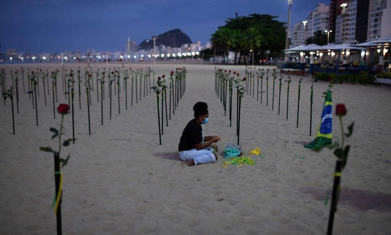 Voluntários espalharam 500 rosas vermelhas nas areias para lembrar o total de mortes Foto: LUCAS LANDAU / REUTERS