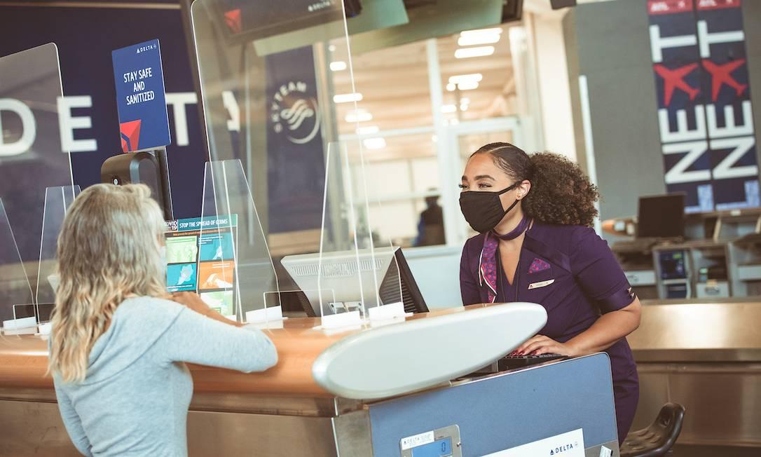 Funcionária da Delta recebe passageira durante o check-in: companhia aérea americana desenvolveu seu próprio certificado digital contra Covid-19 Foto: Chris Rank / Rank Studios / Divugação