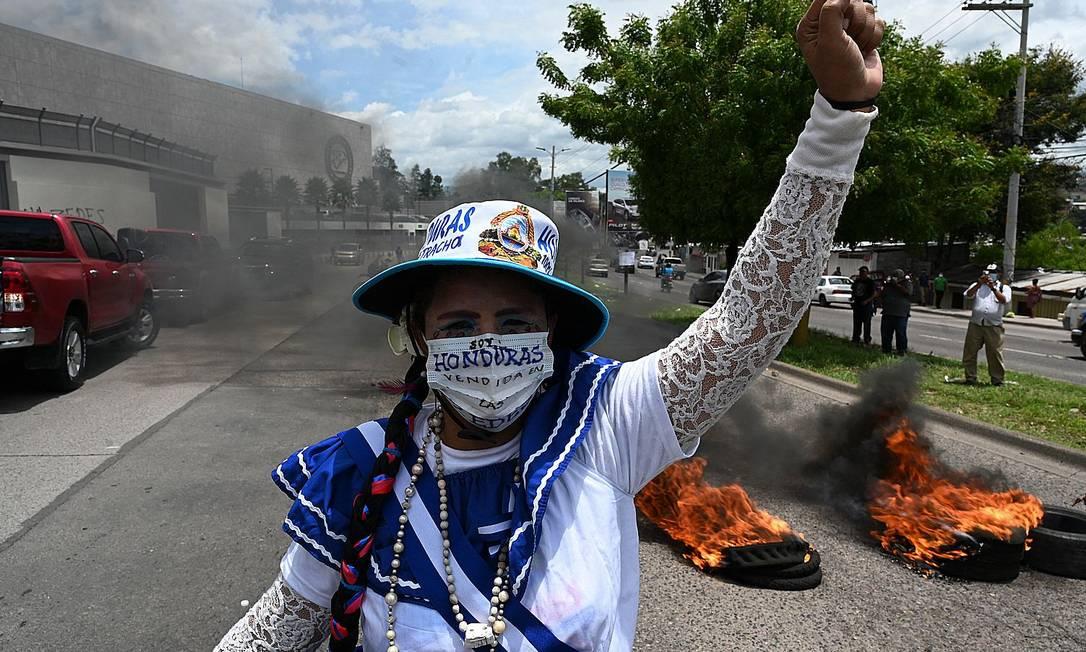 Una donna alza il pugno davanti a una barriera di pneumatici in fiamme durante una protesta contro le zone di lavoro e sviluppo economico (Zedes) - un nuovo tipo di divisione amministrativa - alla periferia della Banca centrale dell'Honduras, a Tegucigalpa, Foto: ORLANDO SIERRA / AFP