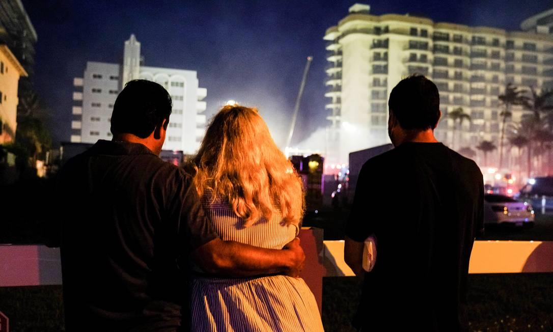 Pessoas assistem ao trabalho das equipes de emergência que continuam as operações de busca e resgate para sobreviventes em Surfside, perto de Miami Beach, Flórida Foto: MARIA ALEJANDRA CARDONA / REUTERS