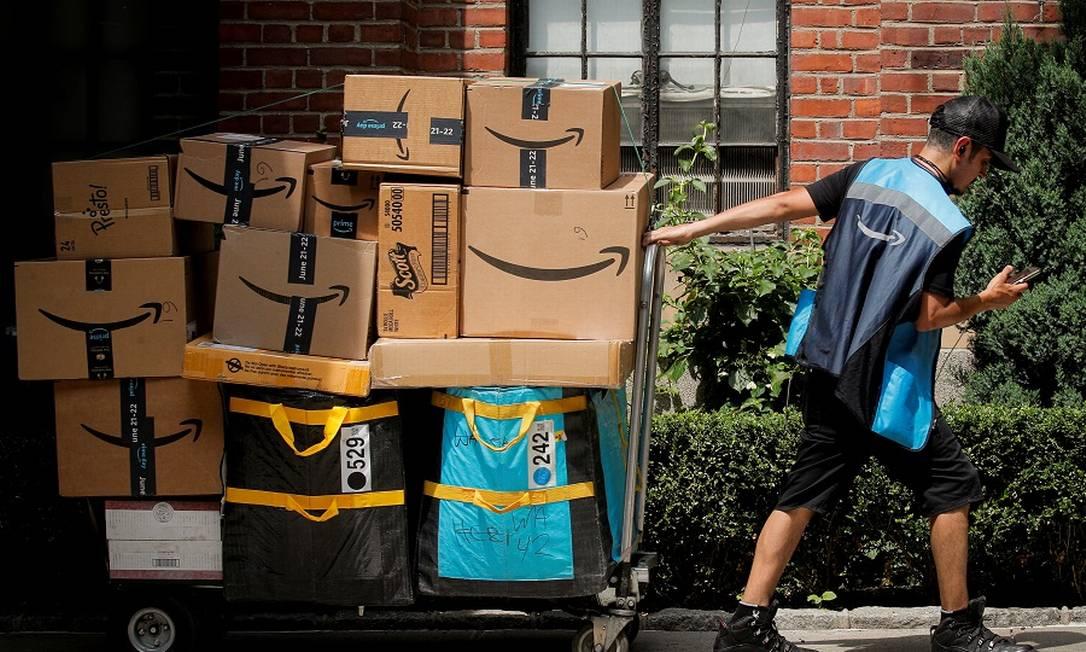 Trabalhador da Amazon com carrinho cheio de encomendas Foto: BRENDAN MCDERMID / REUTERS