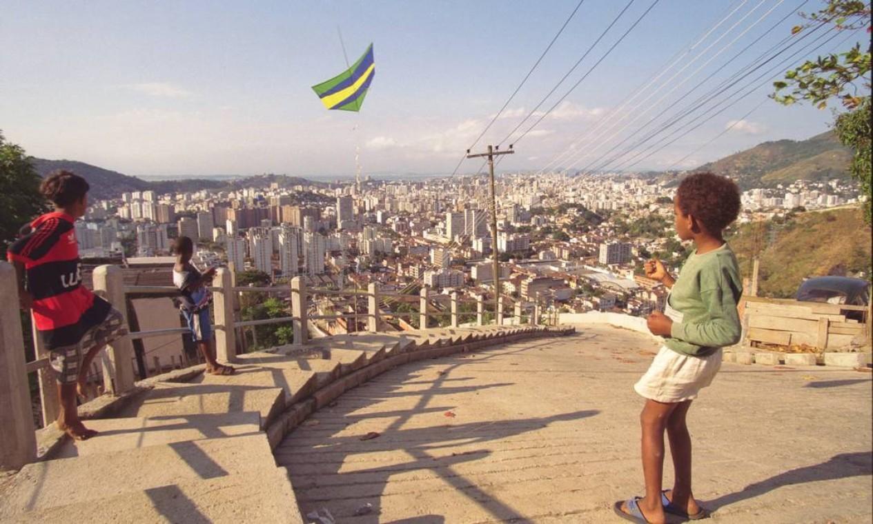 Crianças soltam pipa em rua pavimentada pelo Favela-Bairro no Morro do Borel, na Tijuca, em julho de 1999. Passados 25 anos do início do programa de urbanização, prefeitura planeja quarta etapa, com previsão de investimentos de 300 milhões de dólares através do Banco Interamericano de Desenvolvimento (BID) Foto: Marizilda Cruppe / Agência O Globo