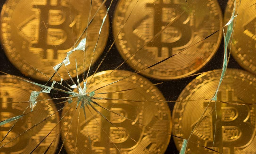 Ilustração representa bitcoins sob um vidro quebrado: moeda digital está na mira de vários bancos centrais Foto: DADO RUVIC / REUTERS/25-6-2021