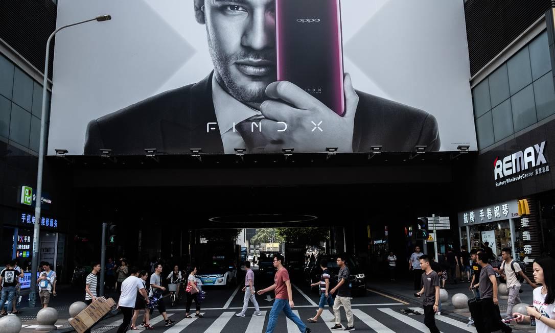 Pedestres sob anúncio da fabricante chinesa de eletrônicos Oppo, em Shenzhen Foto: LAM YIK FEI / NYT/13-09-2018
